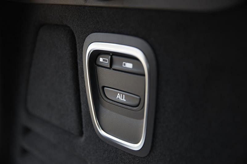 折椅后车厢有一组按钮,只要一按就能折下后排座椅。此功能也能从中控显示屏操作。