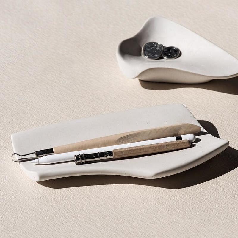 王一龙探索制作有机形状的碟盘,在开着的水龙头下将水泥磨得像肌肤般柔滑。