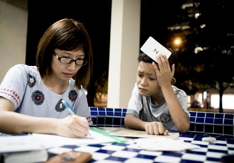 Alif(右)全神贯注地跟大姐姐廖慧雯学英文。(黄淑芬提供)