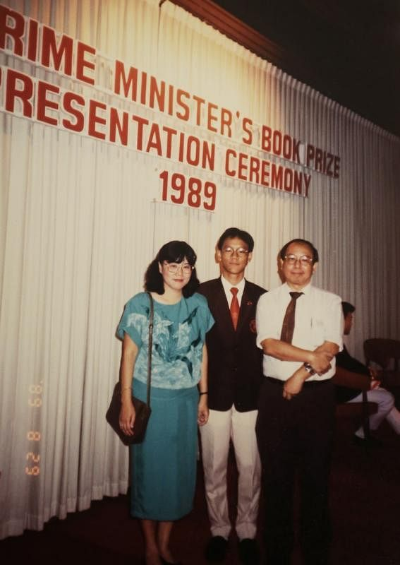 1989年,何国元(中)获颁总理书籍奖与父母合影。(受访者提供)
