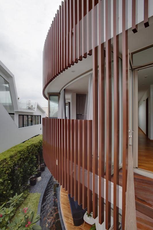 """从一楼到三楼的阳台外缘,铺以褐色直立通风遮阳板,除了有遮阳和通风作用,也给房子外观带来""""又关又开""""的层次感。"""