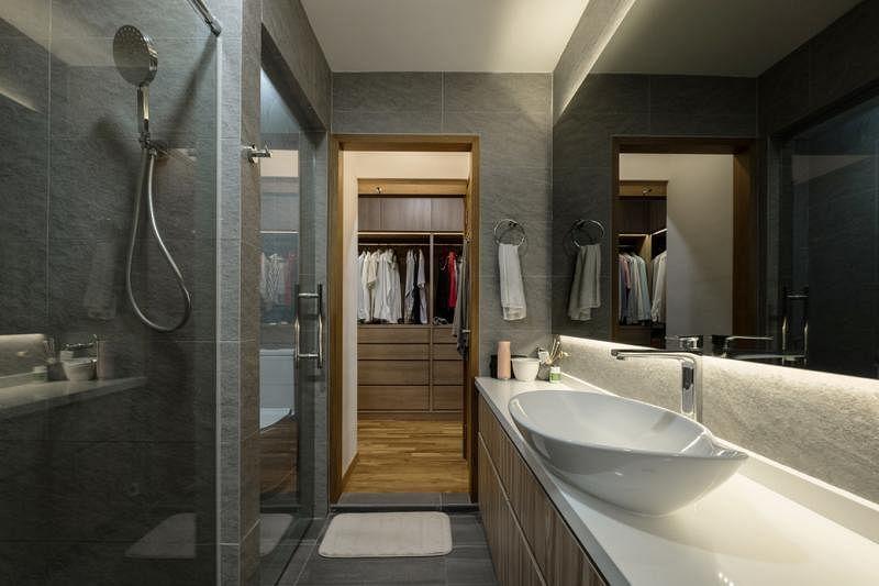 """设计师巧妙地让浴室和主人房共用储物空间,将电视机下隐藏的储物柜""""吃进""""隔壁洗脸盆下的双层橱柜。"""
