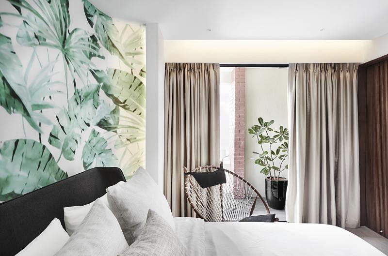 天花板的墙纸装饰主卧室的床头。设计师刻意暴露卧室阳台外的红砖墙,点出复古的热带风情。