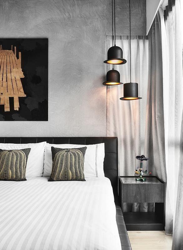 爱帽子的女主人添购了三盏高帽造型的吊灯,设计师都把它们高挂在床头桌之上。