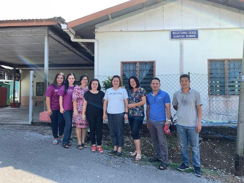 蓝慧敏(右四)与丈夫李家顺(右一)和蓬柏甘榜(Kampung Bumbok)的居民,他们身后的社区中心就是她想要设立肥皂工作室和社区厨房的地方。(陈映蓁摄)