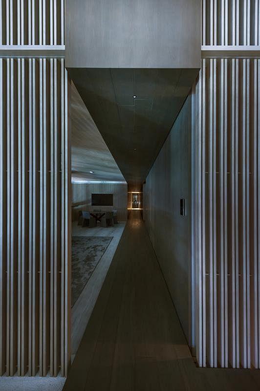 """""""木墙""""后的一道入口通到屋子尽头,尾端还加了一面镜子,让走道更看似永无止境。"""