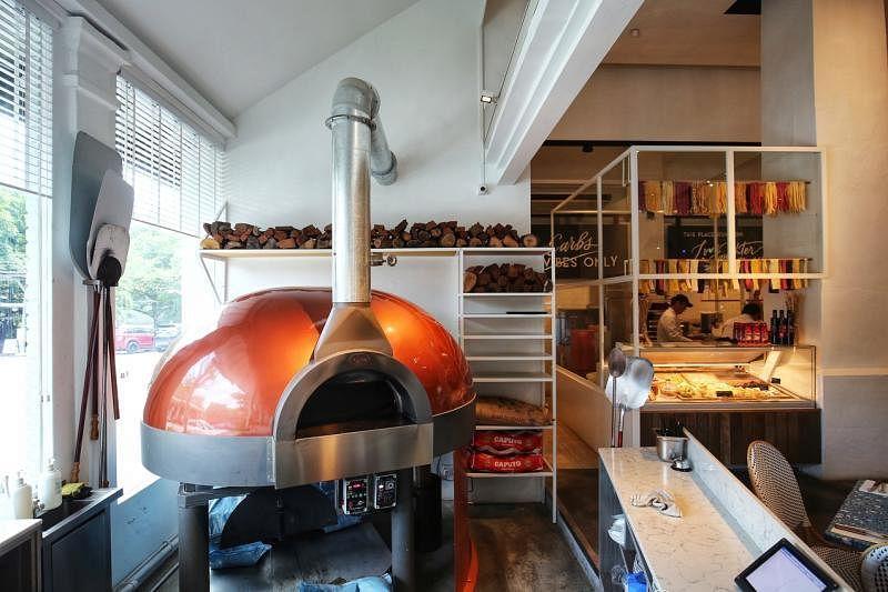特制的木炭烤箱,里头有个自动旋转盘,比萨均匀受热。