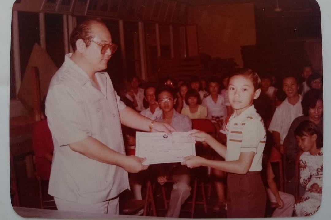 黄炯耀读小六时,从校董手中接获全校模范生奖状。(受访者提供)