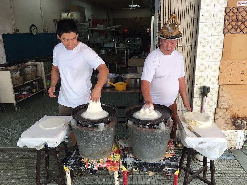 郭金地(左)与父亲(右)父子同心,为家族薄饼生意并肩打拼。(受访者提供)