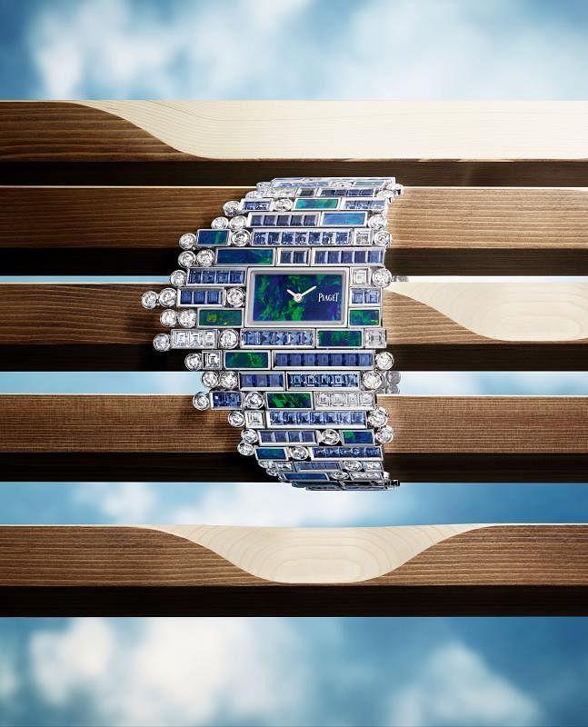 作为Secret Cenote主题的点睛之作,这款手镯腕表以蓝色和绿色呼应热带植被的蓝色与绿色,以深邃的黑色欧泊作为表盘,并在周围用细节点缀,描绘出大自然郁郁葱葱的色彩。在这款腕表中有长方形切割蓝宝石,也有长方形切割和明亮式切割钻石的镶嵌,秉持了伯爵的美学风格。