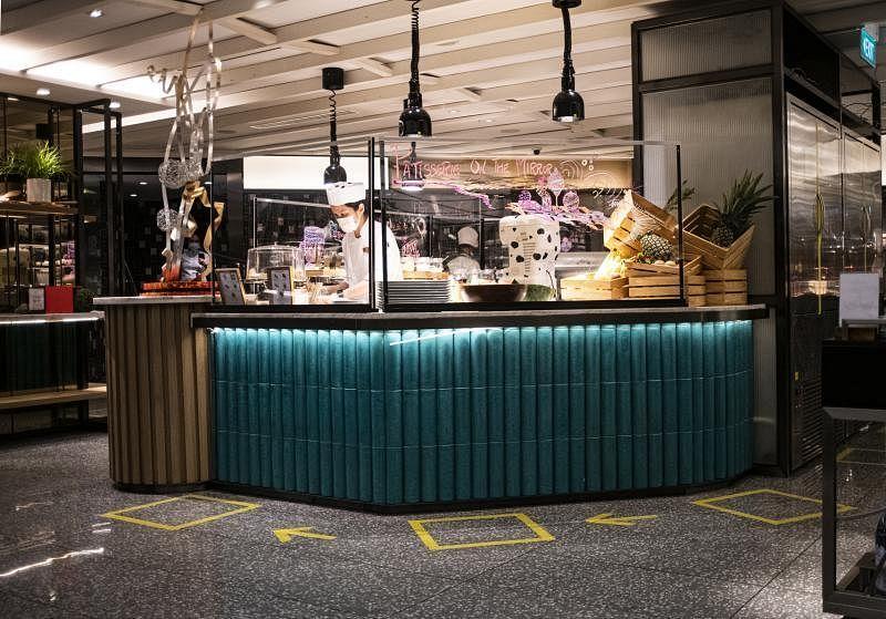 乌节大酒店的乌节咖啡座自助餐烹饪区设置隔屏,地上也分划出站位区。