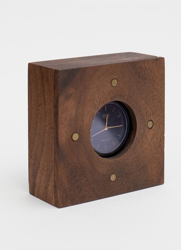 韦玉瀚将断了带的腕表镶在木盒里变成桌钟。