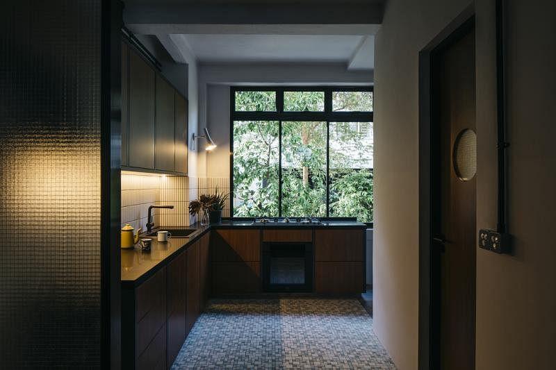 厨房Kit-kat形状的奶白墙面瓷砖与深色的实木壁橱形成有趣的对比。设计师用化学药水洁净厨房地板,还原底下蓝白色马赛克瓷砖。