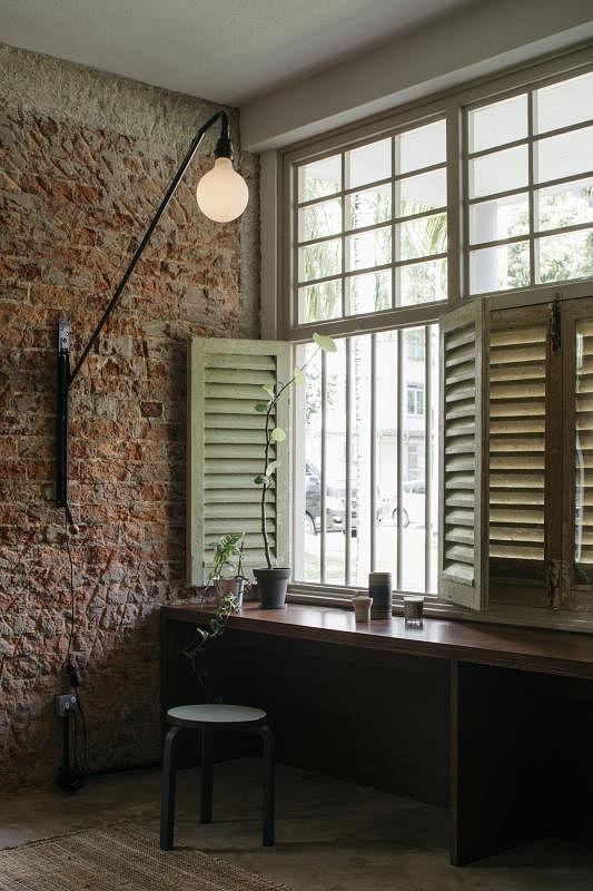 设计师抹掉客厅墙下的石灰,还原美丽的老红砖。这盏高照的灯能做180度左右转动。