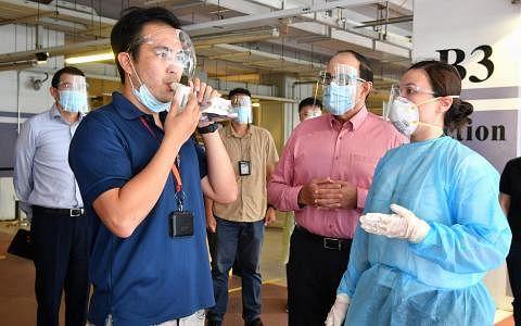 交通部长易华仁(右二)昨天在樟宜机场集团总裁李绍贤(左一)的陪同下观察机场员工如何使用呼吸检测器。机场目前试行让部分员工用呼吸检测器取代抗原快速检测,检测者只须对着检测筒吹气,两分钟内就可得知检测结果。(海峡时报)