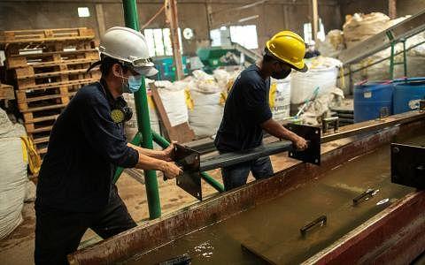 """在社会企业""""塑料火烈鸟""""位于马尼拉的工厂里,工人从模具中取出一块塑料制成的板子。该回收商从餐馆、企业和消费者那里收集塑料,并将其转化为可用的防水板等原材料。(路透社)"""